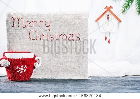 Little mug in wool warmer near the canvas with stiched text 'Merry Christmas'