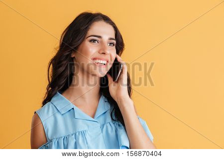 Charming young woman in blue dress talking on cell phone isolated on a orange background
