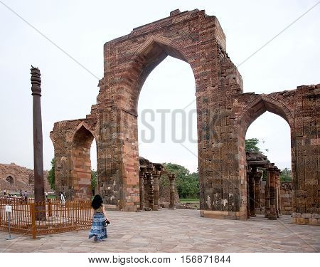 Women visit Iron Pillar at Qutub Minar in Delhi India. Iron Pillar made of 98% wrought iron and has stood 1600 years without rusting or decomposing.