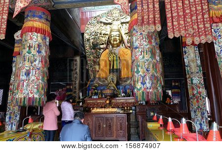 BEIJING - FEBRUARY 25, 2016: Buddhists worship buddha at the Lama Temple Yonghe Lamasery. It is one of the largest and most important Tibetan Buddhist monasteries in the world in Beijing, China.