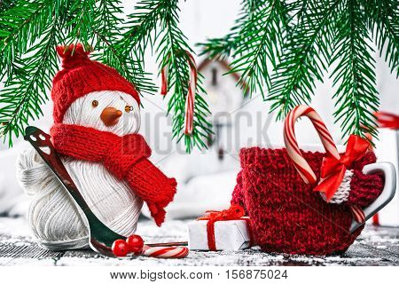 Handmade yarn snowman holding teaspoon and cozy cup holding candy cane under evergreen branches