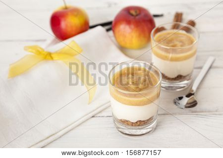Christmas dessert with cinnamon-flavored applesauce, vanilla-flavored cream and cake crumbles in a glass, arranged with ingredients on table