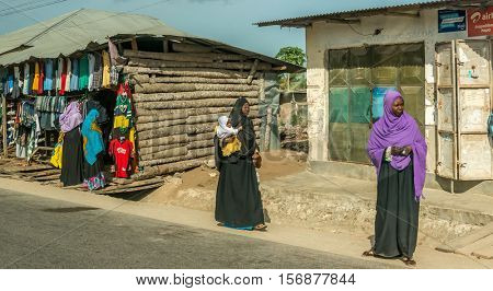 ZANZIBAR, TANZANIYA- JULY 12: people near a clothing store by village road on July 12, 2016 in Zanzibar