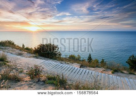 Sunset over Lake Michigan shines its light on this boardwalk on Empire Bluff Trail near Empire Michigan. This trail overlooks Sleeping Bear Dunes