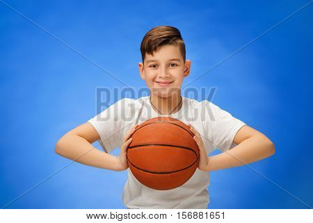 Adorable 11 year old boy child with basketball ball on blue background.