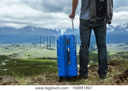 Man with suitcase stands on mountains backdrop. Travel concept