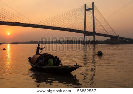 Wooden boat on river Hooghly at sunset with Vidyasagar bridge at the backdrop (silhouette), These country boats are used for pleasure boat rides on the river.