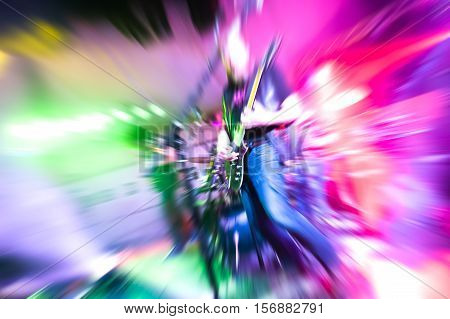 colorful motion zoom abstract of a guitarist playing on stage