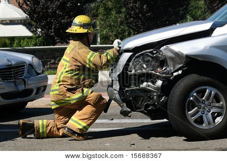 Firefighter opening the hood of a car after a car accident