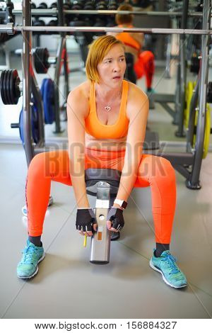 Middle-aged woman in orange rests after training in modern gym, shallow dof