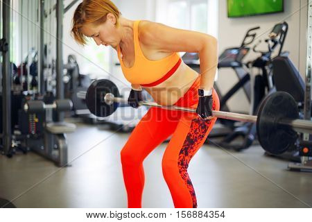 Middle-aged woman in orange lifts weight in modern gym with simulators, shallow dof
