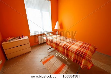 Empty orange room with table for massage, aromatherapy and relaxation
