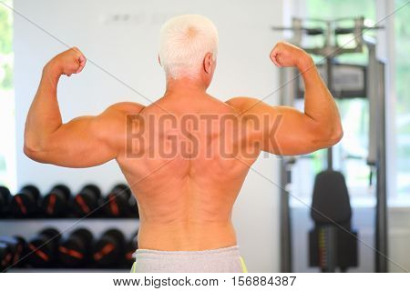 Middle-aged instructor shows his muscles in gym, back view, shallow dof