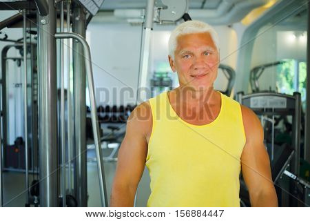 Middle-aged instructor stands in modern gym with fitness equipment
