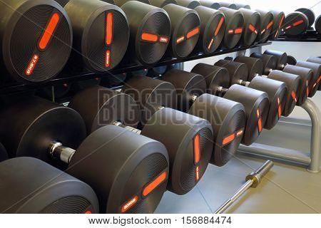Set of heavy black dumbbells for men on rack in modern empty gym