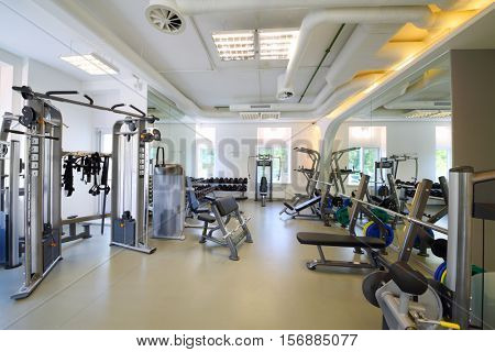 Empty modern gym with fitness equipment, mirror for sport training