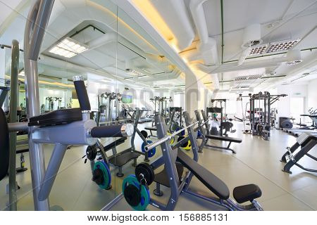 Empty modern gym with new shiny fitness equipment, big mirror for sport training