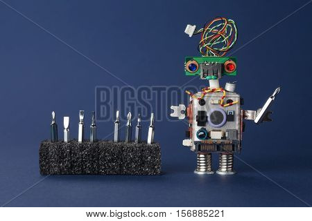 Retro style robot repairman with screw drivers hardware toolkit. Technician service concept. Copy space dark blue background