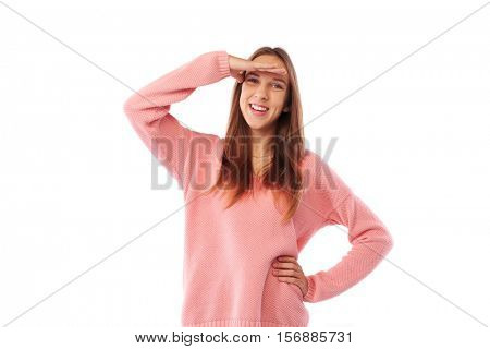 Mid shot of beautiful young casual teen with hand on forehead looking into distance posing isolated over white. Looking at something or someone