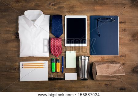 Business objects on the desk, including digital tablet, shirt, ties, lunch box, paper and pencils, top view