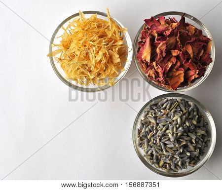 Dried marigold (calendula) petals with lavender and rose for beauty treatments in clear glass bowls -  top view with copy space