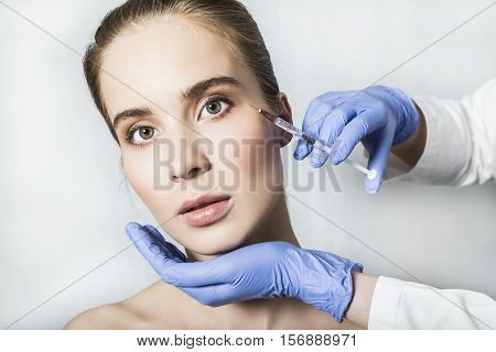 Doctor aesthetician in blue medical gloves makes hyaluronic acid beauty injections in the periorbital areas of female patient