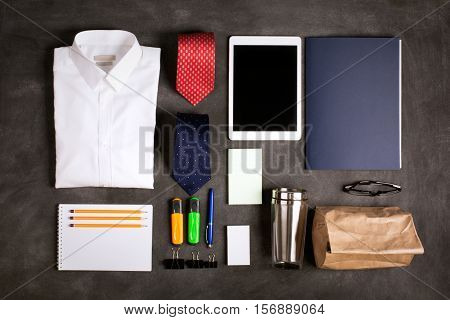 Business objects on the desk, including digital tablet, shirt, ties, lunch box, paper and pencils, top view, black chalkboard