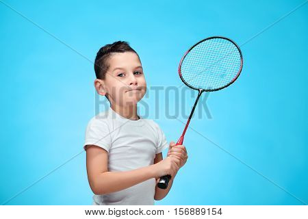 Boy with badminton racket standing against blue studio background