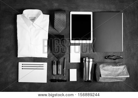 Business objects on the desk, including digital tablet, shirt, ties, lunch box, paper and pencils, top view. Black and white image