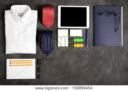 Business objects on the desk, including digital tablet, shirt, ties, lunch box, paper and pencils, top view with copy space. Black chalkboard as background
