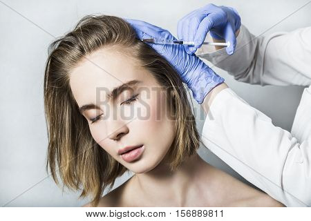 Doctor aesthetician in blue medical gloves makes hyaluronic acid rejuvenation beauty injections in the back of the head of beautiful young female patient for hair growth and to prevent boldness. poster
