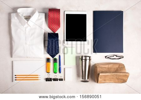 Business objects on the desk, including digital tablet, shirt, ties, lunch box, paper and pencils, top view. White background