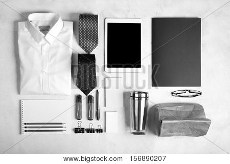 Business objects on the desk, including digital tablet, shirt, ties, lunch box, paper and pencils, top view.White background, black and white image