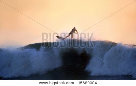 A surfer riding a big wave at sunset