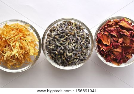 Dried marigold (calendula) petals with lavender and rose for beauty treatments - in clear glass bowls
