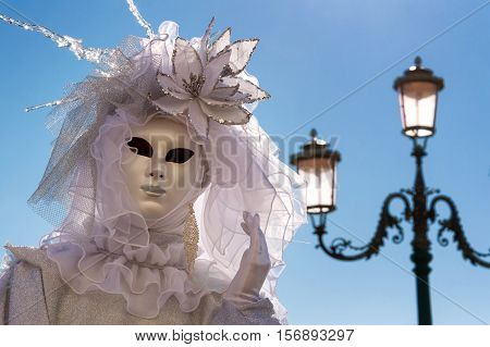 VENICE, ITALY - FEBRUARY 16, 2015: Venetian mask posing with a traditional venetian lamp on the background