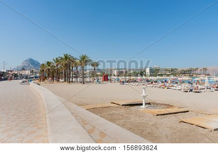 Xabia, Spain - September 7, 2016: Sunbathers on beach-loungers enjoy hot day on beautiful Mediterranean beach on Costa Blanca Spain