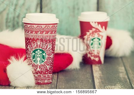 DALLAS TX - NOVEMBER 15 2016: A cup of Starbucks popular holiday beverage served in the new 2016 designed red holiday cup. Displayed with Christmas hats on wooden rustic table. Vintage filter effects.