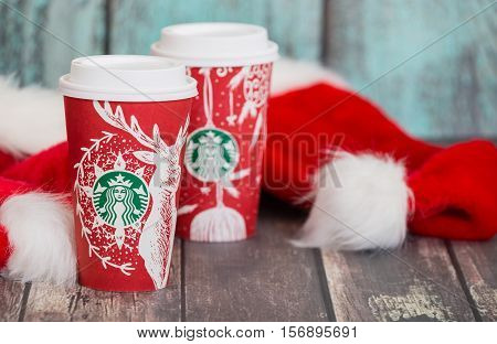 DALLAS TX - NOVEMBER 15 2016: Starbucks popular holiday beverages served in the new 2016 designed red holiday cups. Displayed with Christmas hats on wooden rustic table.