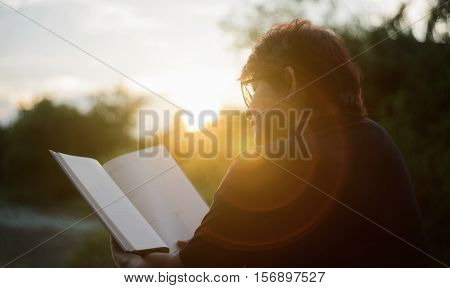 Asian Mature Woman Reading A Book At Sunset Moment.blurred Sunset In Background.silhouette Woman Rea