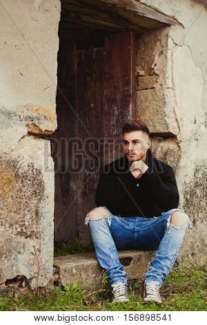 Attractive guy in a old house with black jersey