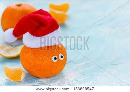 Tangerine with eyes in Santa hat Christmas Xmas New Year concept fresh ripe and sweet mandarin orange clementine tangerine symbol winter holidays