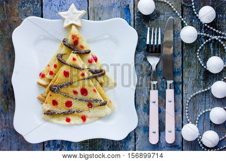 Delicious breakfast crepes shaped Christmas tree with chocolate and jam on old wooden table top view
