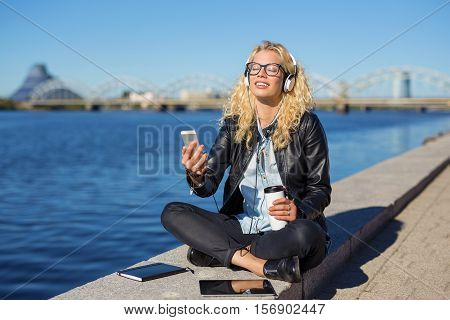 Woman ejoying the music in her headphones from smartphone