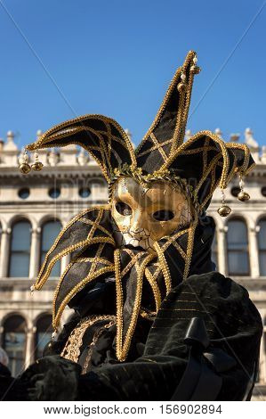 VENICE, ITALY - FEBRUARY 16, 2015: Jester masked model in San Marco square at Venice carnival