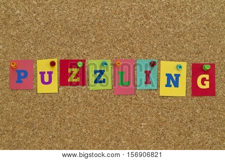 Puzzling word written on colorful sticky notes pinned on cork board.
