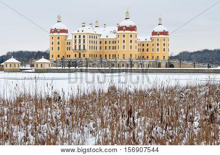 Moritzburg castle in background of lake in winter time
