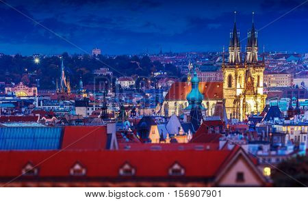 Church of Our Lady Before Tyn among roofs old houses in Prague city town. Czech Republic. Evening illumination for buildings and nighttime blue sky after sunset