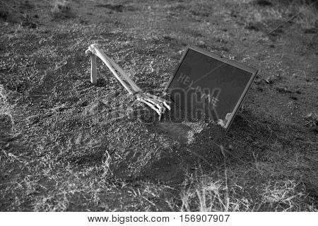 Crime Scene. A skeleton arm reaches out of a grave to type a clue on a computer. Murder scene