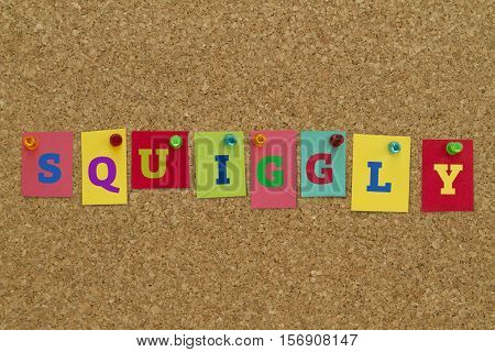 Squiggly word written on colorful sticky notes pinned on cork board.